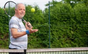 healthy older man playing tennis